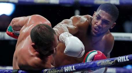 Anthony Joshua, right, hits Kubrat Pulev during their