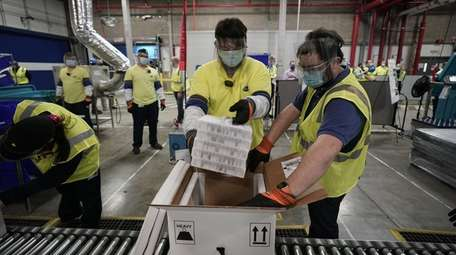 Workers pack vials of Pfizer's COVID-19 vaccine for