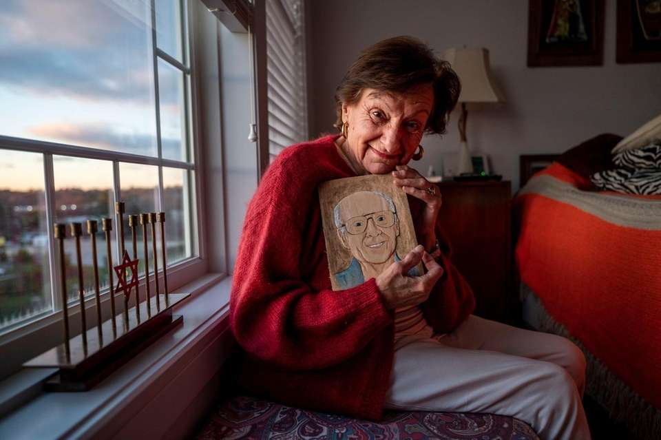 Marsha Elowsky poses with a carved wooden potrait