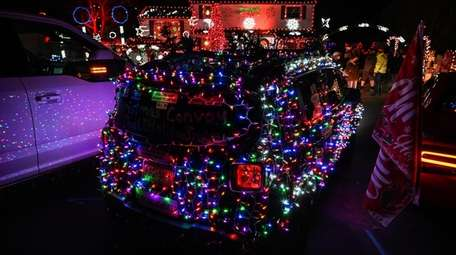Cars are dressed in Christmas lights during the