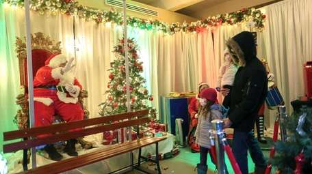 Santa greets guests from behind a plexiglass window
