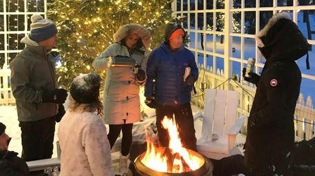 People enjoy an outdoor fire at the Cedar
