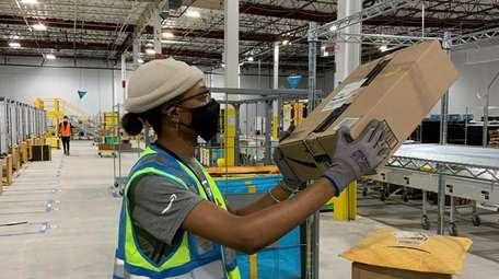 Crystal A. Anthony sorts packages at Amazon's last-mile