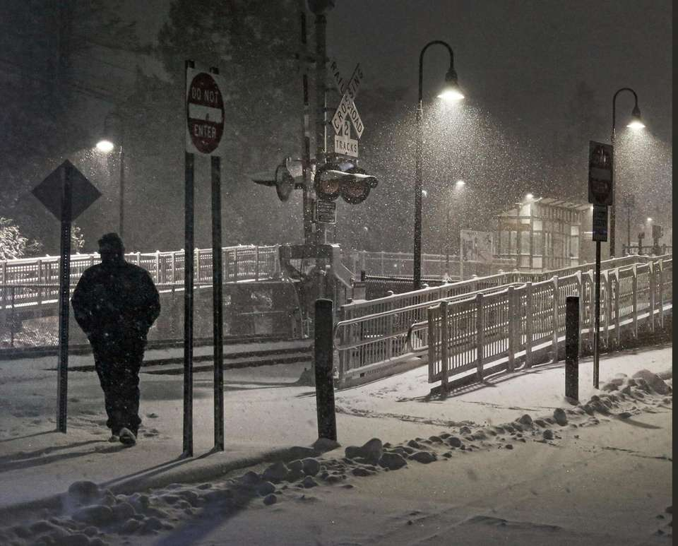 A lone passenger crosses the tracks at the