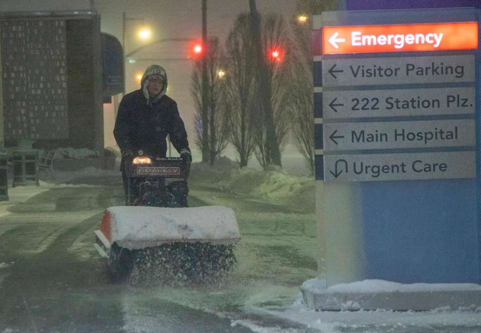 A man tries to clear the sidewalk on