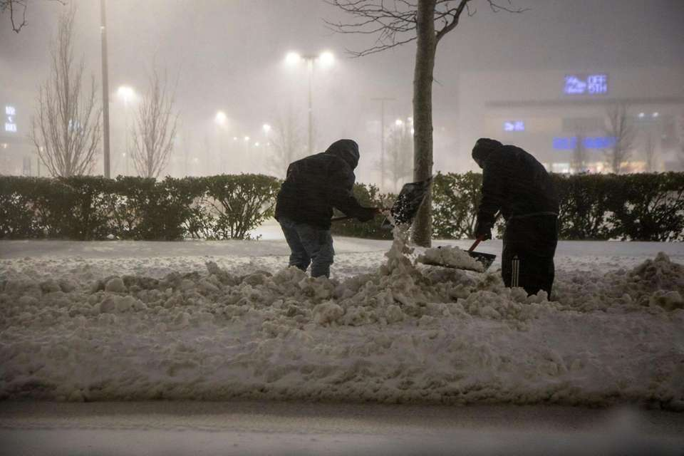 2 men try to clear the sidewalk on