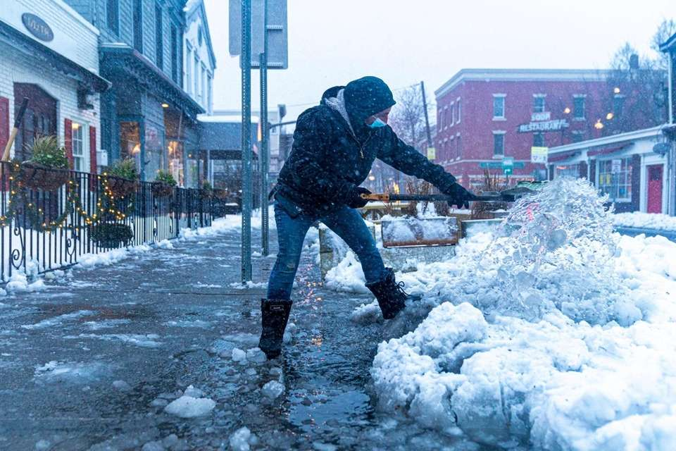 A man shovels snow and ice on Main