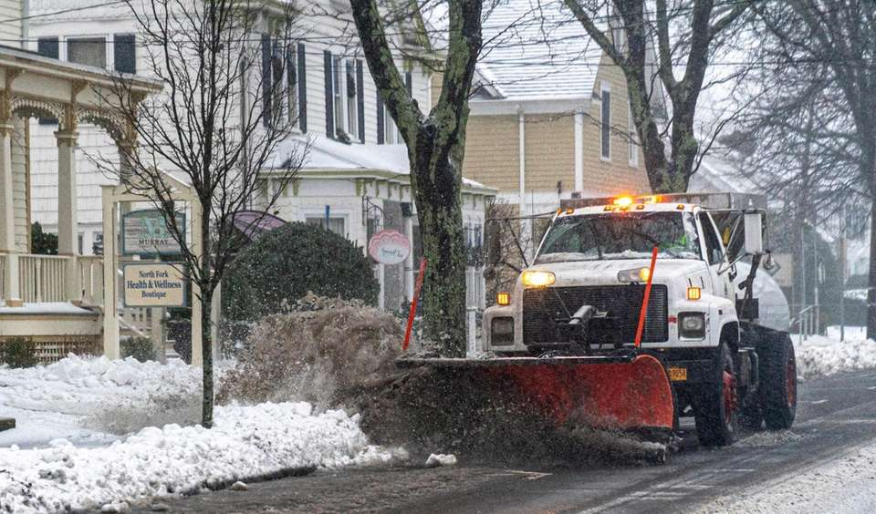 A plow clears snow from the roadway on