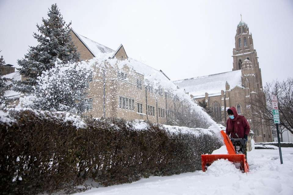 Miguel Angel works on clearing the sidewalk outside