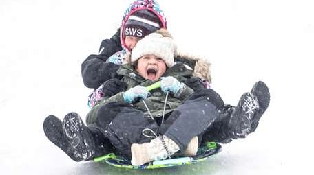 Two 10-year-olds sled down a hill at Cedar