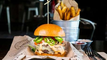 An elk burger with pepper jack cheese, lettuce,