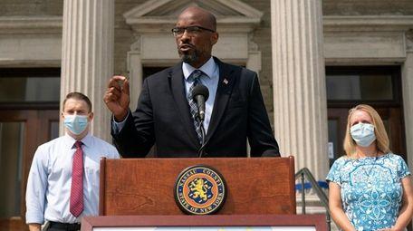 Nassau County Legislature Minority Leader Kevan Abrahams, center,