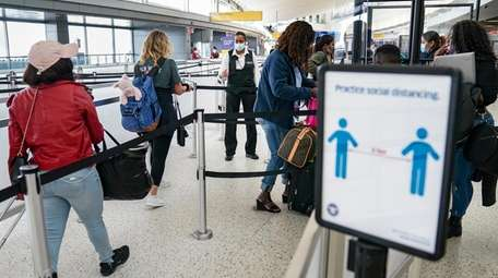 Transportation Security Administration personnel and travelers observe COVID-19