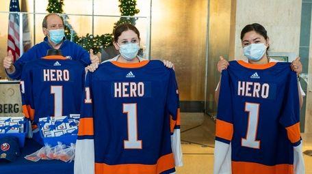 Islanders co-owner Jon Ledecky, left, poses with nurses