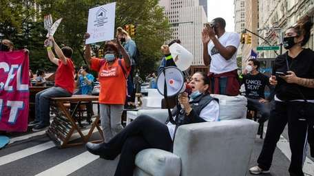 Demonstrators hold signs and sit on furniture placed