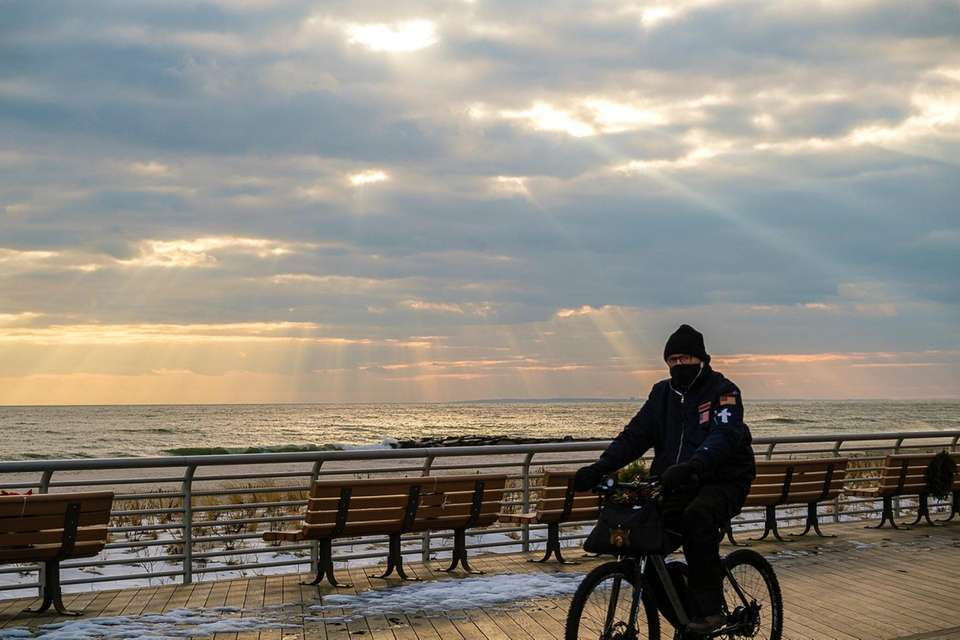 A bicyclist pedals along the boardwalk as faint