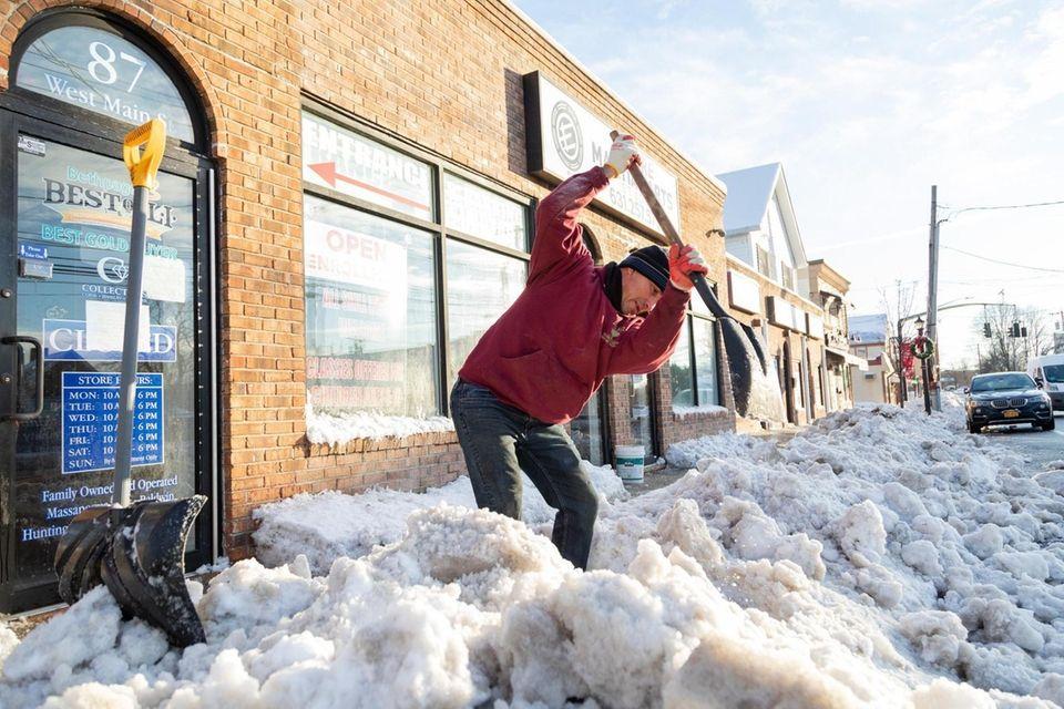 Carlos Ramos shovels the sidewalk along West Main