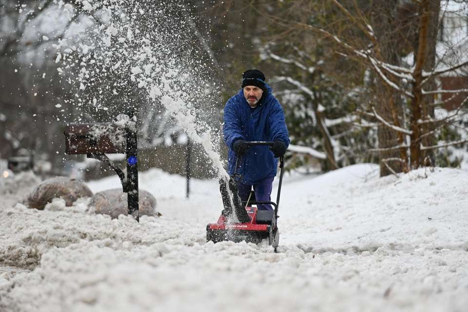 Tuna Djemil uses a snow blower to clear