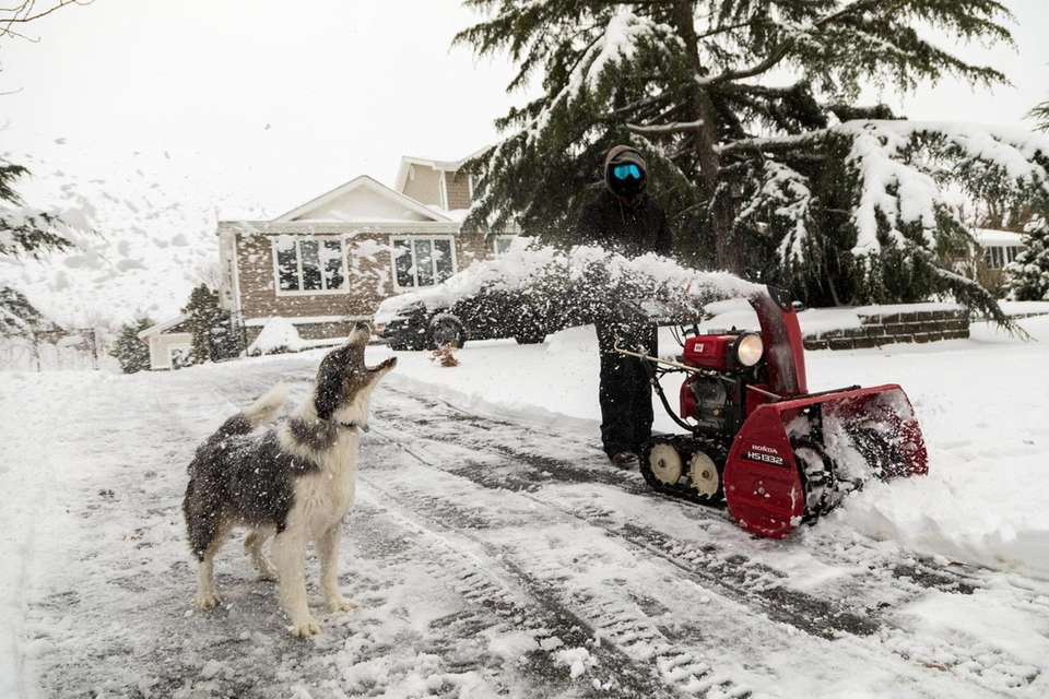Paul Zucconi uses a snow blower to clear