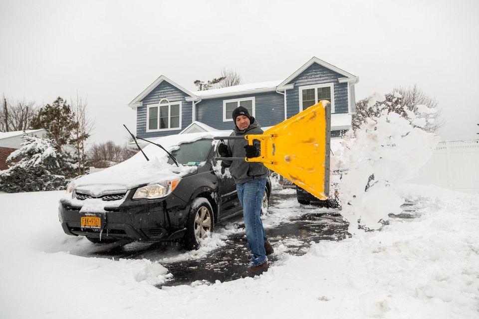 Aaron Perretta shovels the driveway of his home