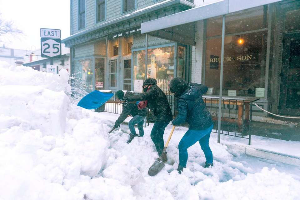 People shovel snow and ice on Main Street