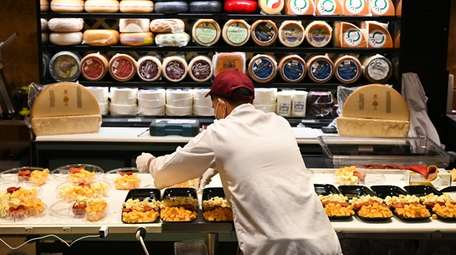 Cheese is prepared at the cheese counter inside