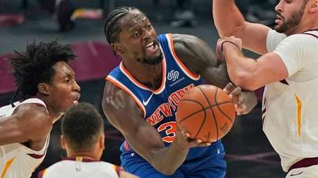 The Knicks' Julius Randle, center, tries to get