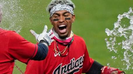 Cleveland's Francisco Lindor, right, tosses water on Jose