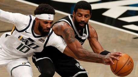 Kyrie Irving of the Nets battles for the