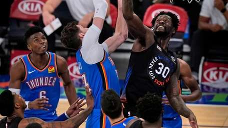 The Knicks' Julius Randle, right, fights for a