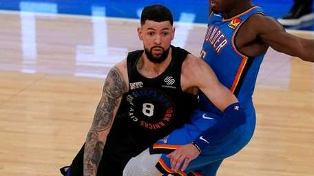 The Knicks' Austin Rivers, left, pushes past theThunder's