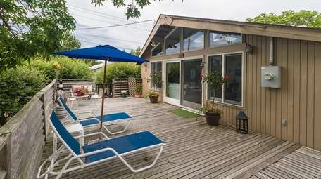 Priced at $849,000, this three-bedroom, two-bathroom wood-sided bungalow
