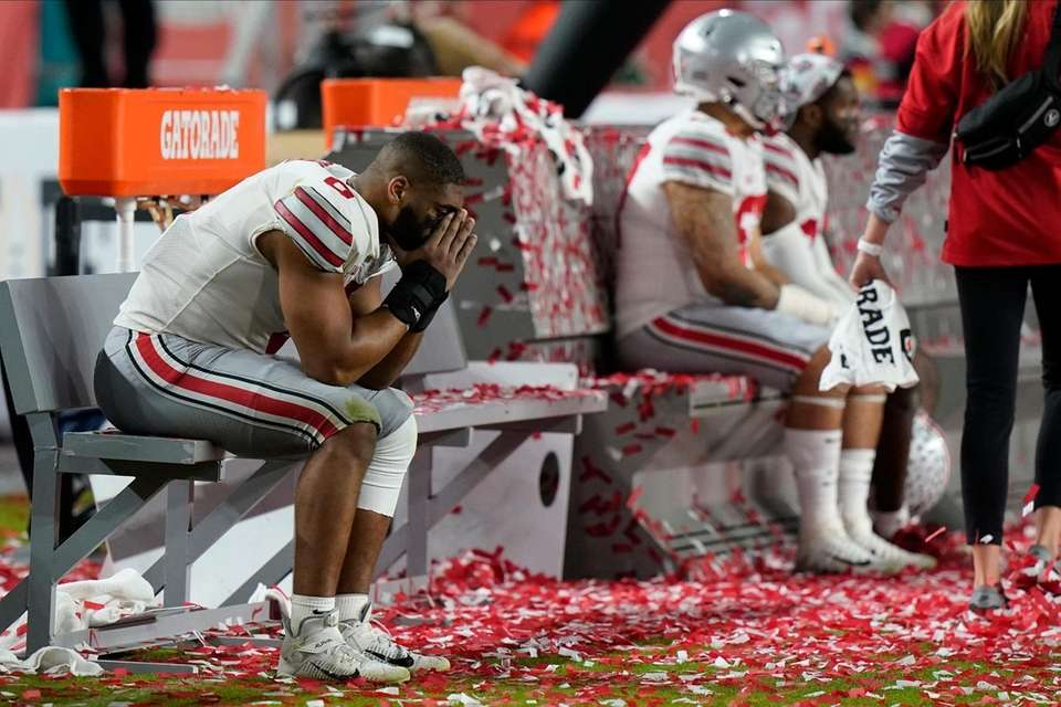 Ohio State players sit on the bench after