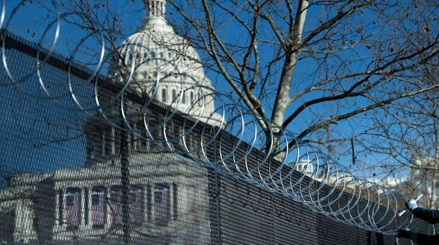 Razor wire is added Thursday atop a fence