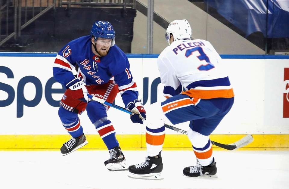 The Rangers' Alexis Lafreniere works against the Islanders'