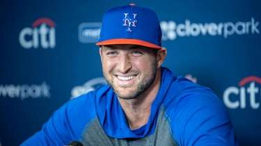 Mets player Tim Tebow talks to the media