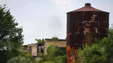 A water tower and three vacant buildings on