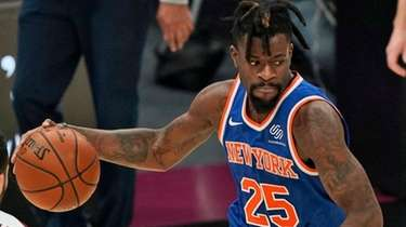 The Knicks' Reggie Bullock drives between the Cavaliers'