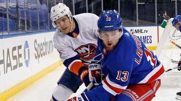 The Islanders' Ryan Pulock, left, checks the Rangers'