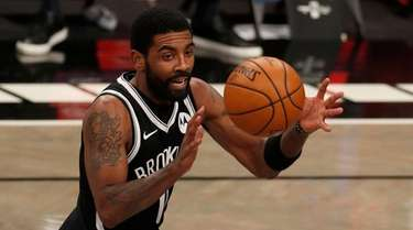 Kyrie Irving #11 of the Nets controls the