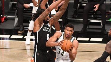 Milwaukee Bucks forward Giannis Antetokounmpo is defended by