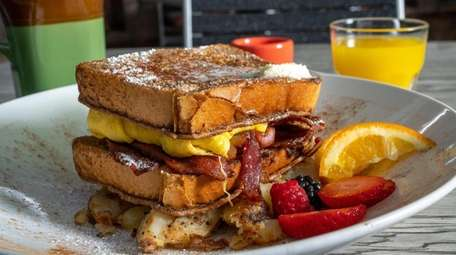French toast stacked with bacon and eggs at