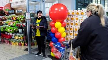 A greeter at Lidl welcomes a shopper at