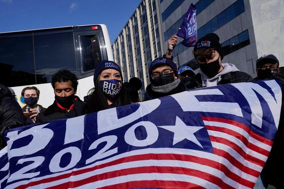 President Joe Biden supporters wave flags near the