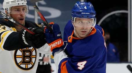 Andy Greene of the Islanders defends against Charlie