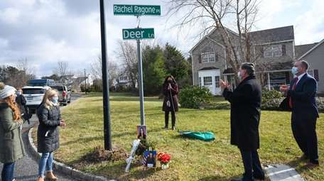 Kim Ragone, center, seen praying, at the intersection