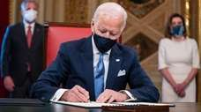 President Joe Biden signs documents including an inauguration