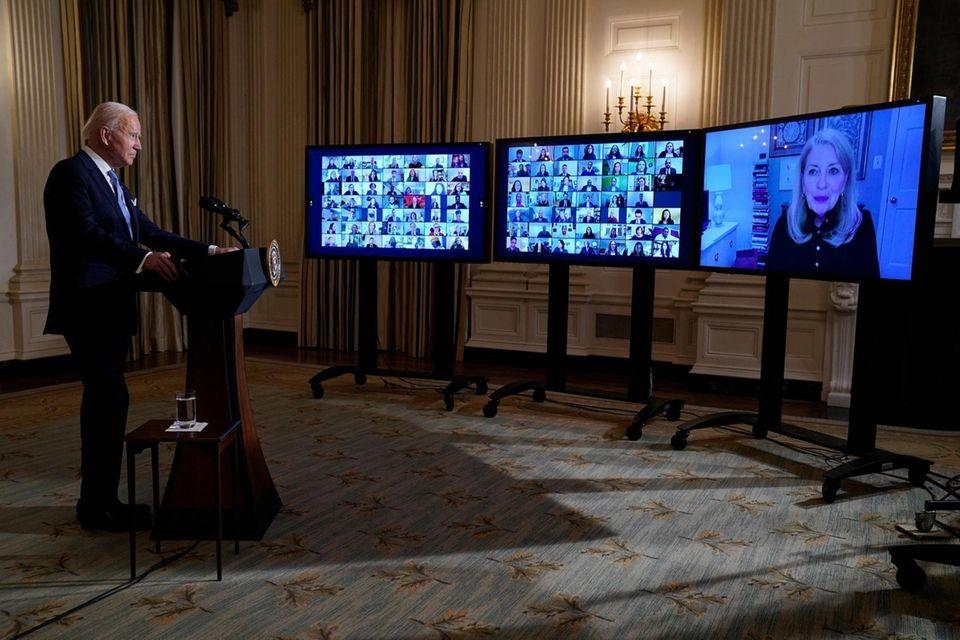 President Joe Biden listens during a virtual swearing