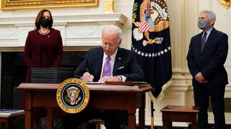 President Joe Biden signs executive orders after speaking