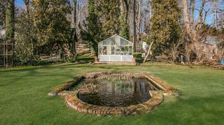The property has a 3-stall barn, greenhouse and